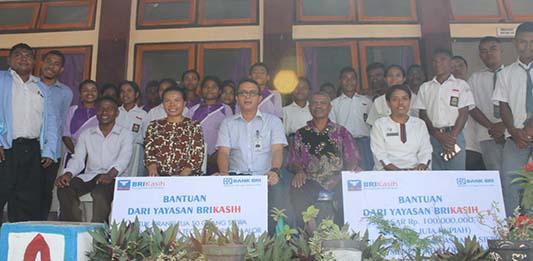 Pimpinan Cabang BRI Kalabahi Nartha Simamora, pose bersama Ketua Yayasan Sangkakala Liem Odja, Waket Komite Markus Laan, Kepala SMTK Endang Kaminukan, para guru dan siswa.
