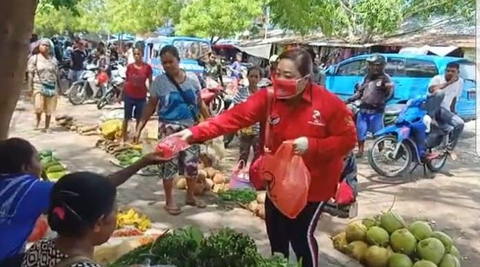 Ketua DPRD Alor Enny Anggrek sedang membagi Masker di Pasar Kadelang, Kamis (2/4/2020).