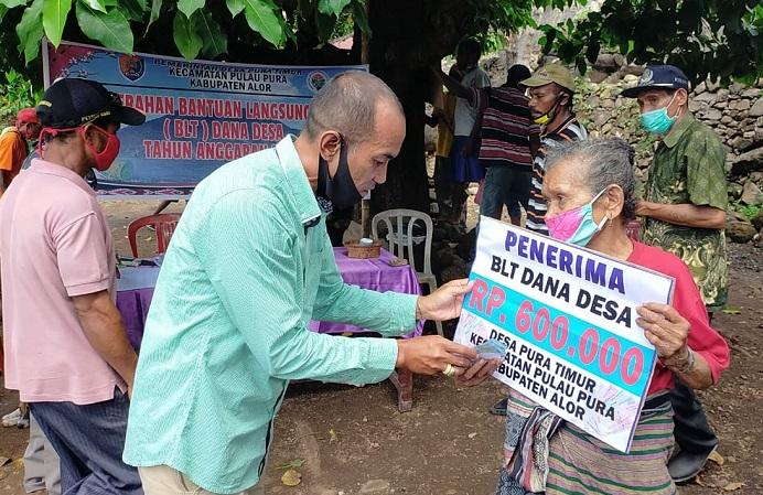 Tenaga Ahli Desa Kabupaten Alor Machris Mau, SP, serahkan BLT Dana Desa secara simbolis kepada warga Desa Pura Timur, Senin (25/5) di Desa Pura Timur.