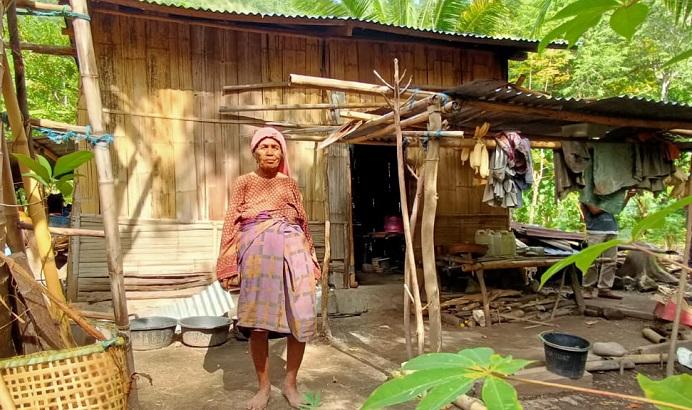 Oma Aizah Dursaha sedang berdiri membelakangi rumahnya di RT 5 RW 4 Desa Alila Timur Kecamatan Kabola, Kabupaten Alor, NTT.