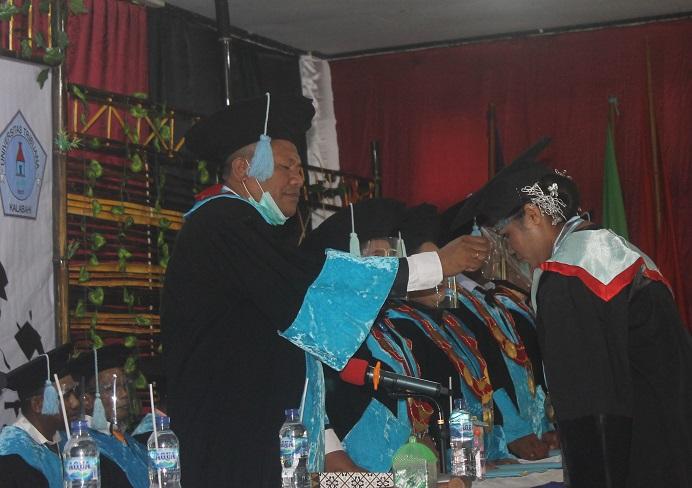 Rektor Untrib Alvons F. Gorang, S.Sos.,MM meminda tali toga wisudawan terbaik, Desimina Iriyanti Wabang, S.Pd pada Rabu (28/10/2020) di Aula Pola Tribuana Kalabahi.