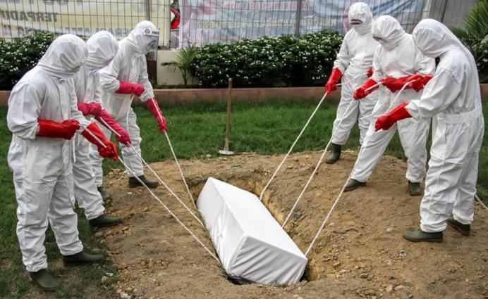 Gambar: Ilustrasi pemakaman jenazah pasien Covid-19. (Foto: detik.com).