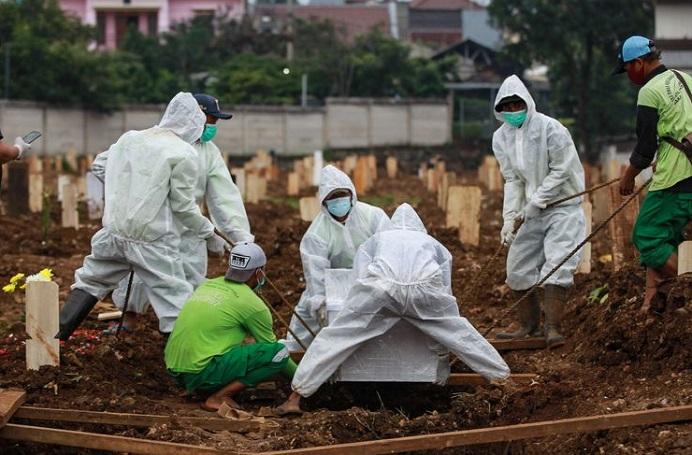 Petugas memakamkan jenazah pasien Covid-19 di TPU Srengseng Sawah, Jakarta Selatan, Senin (25/1/2021). (Foto: Kompas.com).