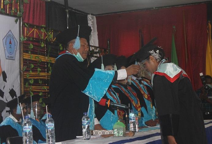 Rektor Untrib Alvons F. Gorang, S.Sos.,MM meminda tali toga wisudawan terbaik, Desimina Iriyanti Wabang, S.Pd pada Rabu (28/10/20) di Aula Pola, Kalabahi.