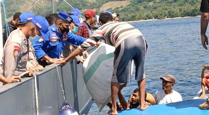 Suasana pembongkaran barang bantuan bencana dari atas kapal KP Barata 8004 Mabes Polri di Desa Kaleb Pantar Timur, Senin (19/4).