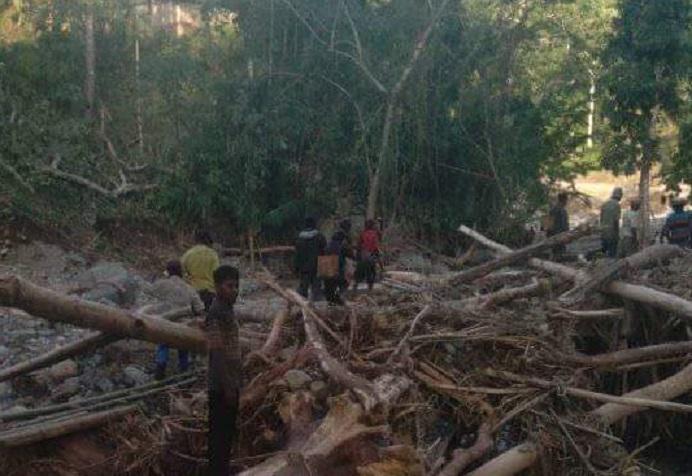 Warga menggotong Jasad korban bencana alam, Ibu Nila Letde-Maure melewati kali menuju desa setempat untuk dimakamkan pada Kamis (8/4) siang.