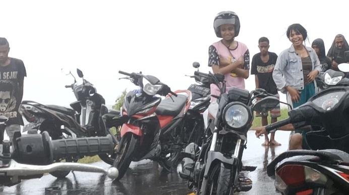 Pengguna jalan sedang antrian menunggu motornya diangkut pemuda setempat melewati banjir