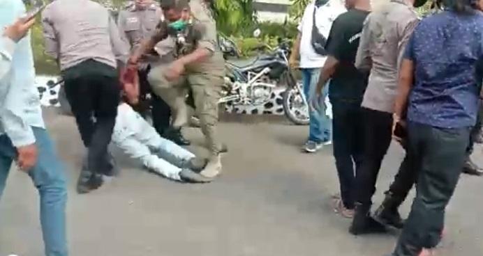 Gbr: Tangkapan layar video seorang oknum Anggota Polres Alor dan Pol PP diduga memukul dan menginjak demonstran mahasiswa yang berdemonstrasi menentang kebijakan pemerintah merelokasi 753 pedagang di Alor.